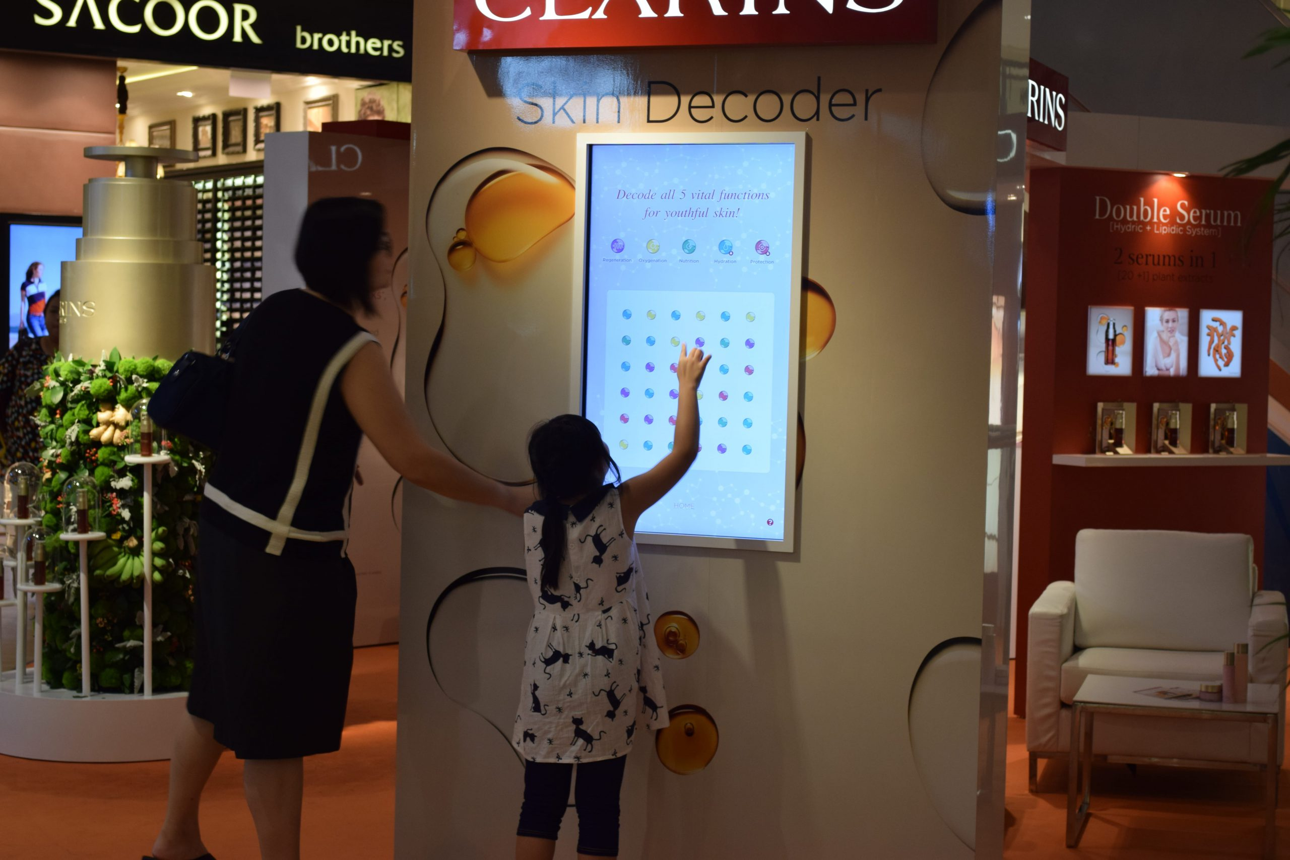 A mum watches on as her daughter plays the clarins digital game (o2o)