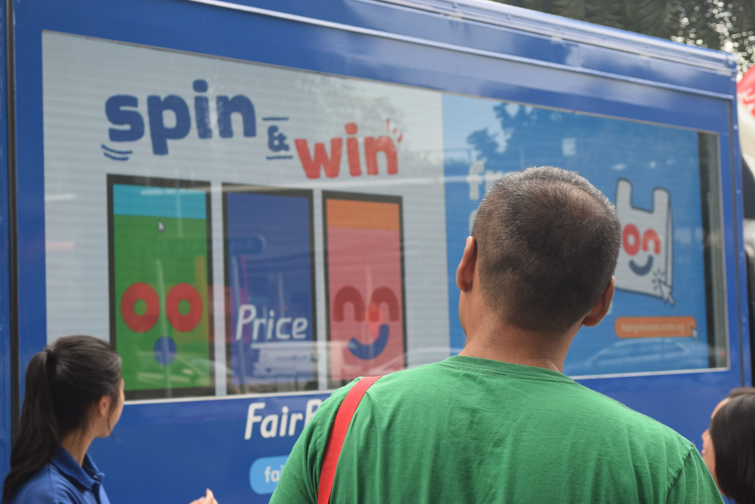 A man listens on as a brand ambassador explains to him how the fairprice on interactive spin and win game works