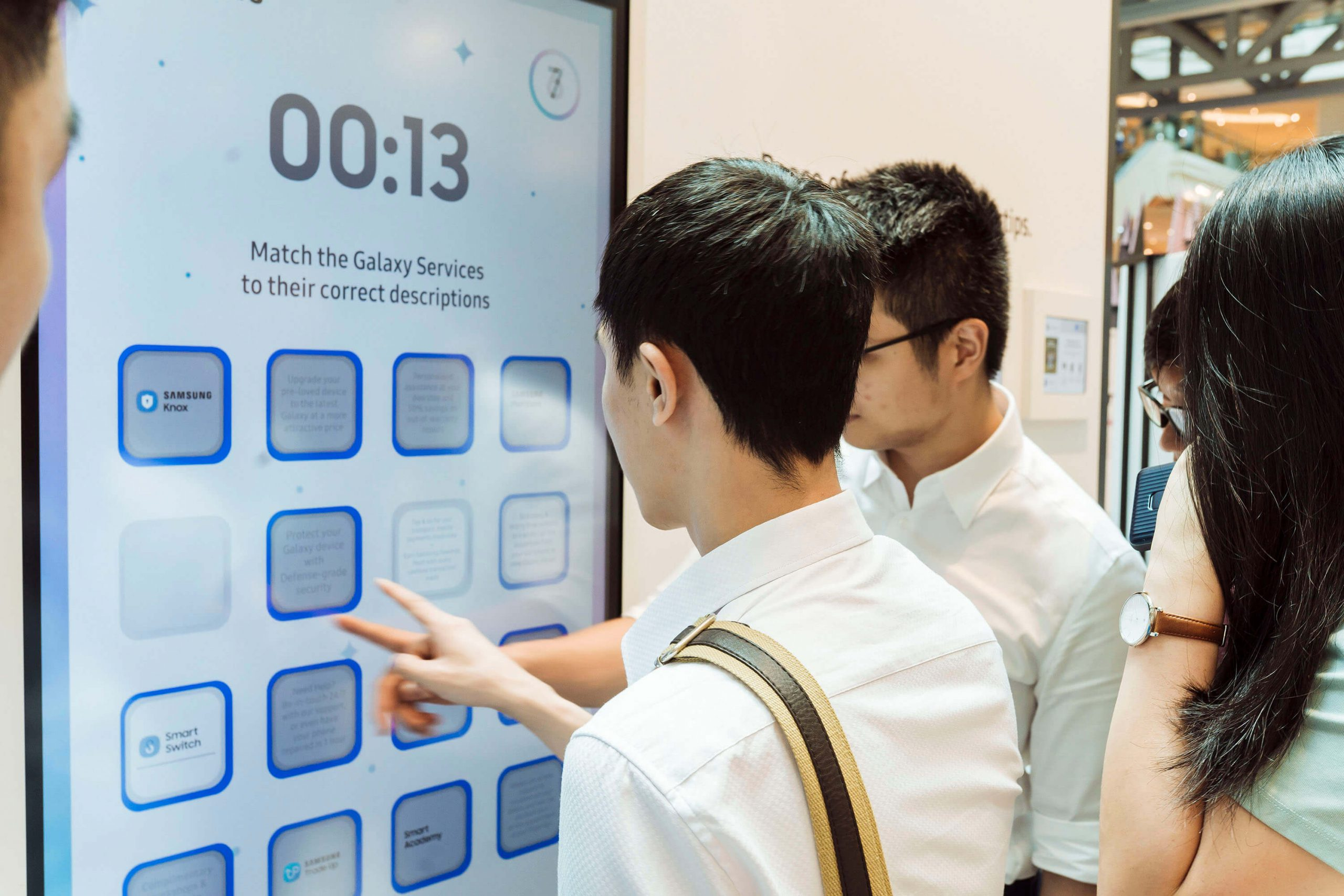 Two men team up to play the Samsung Galaxy Services Memory Game as others watch on