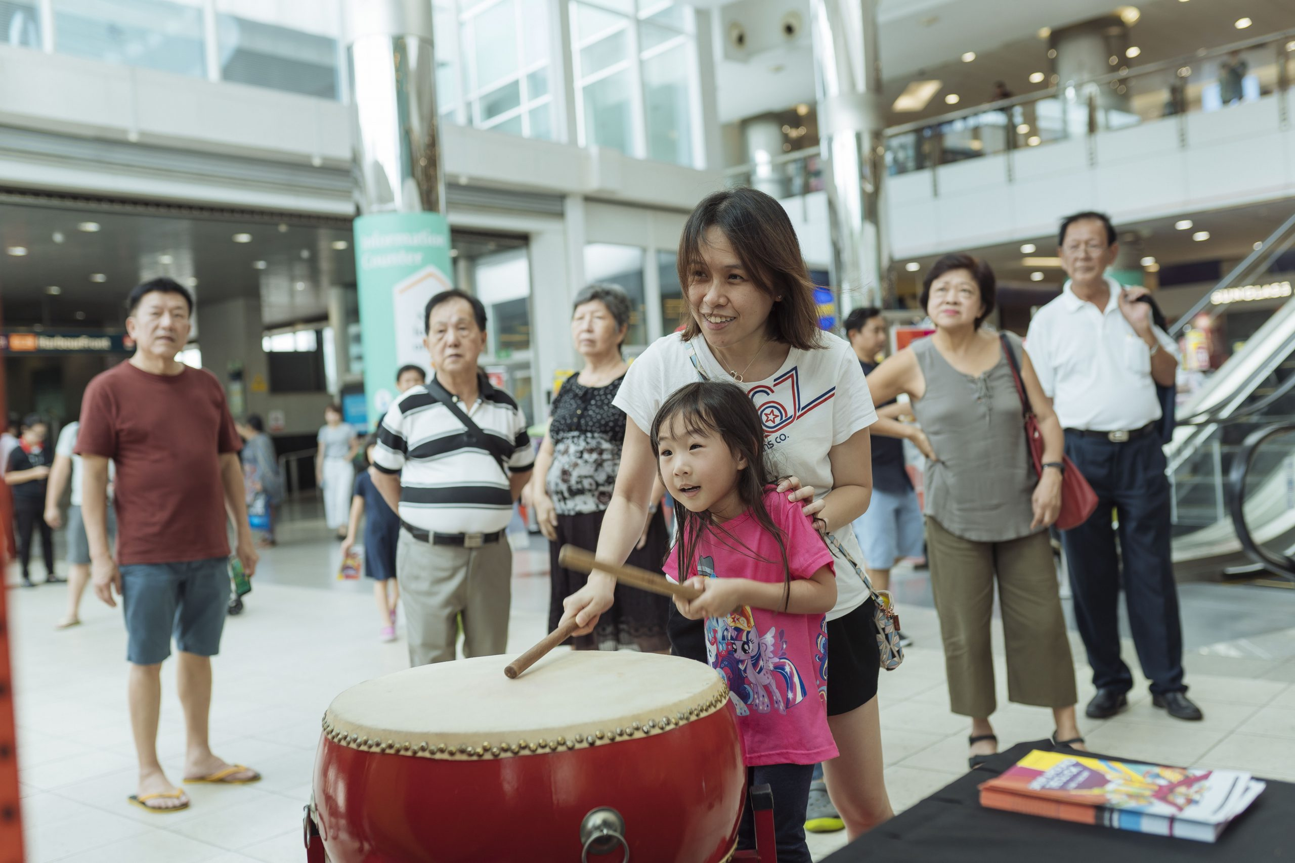 A little girl and her mother team up to play the HBFC Ramen Chomp Digital Drum Game