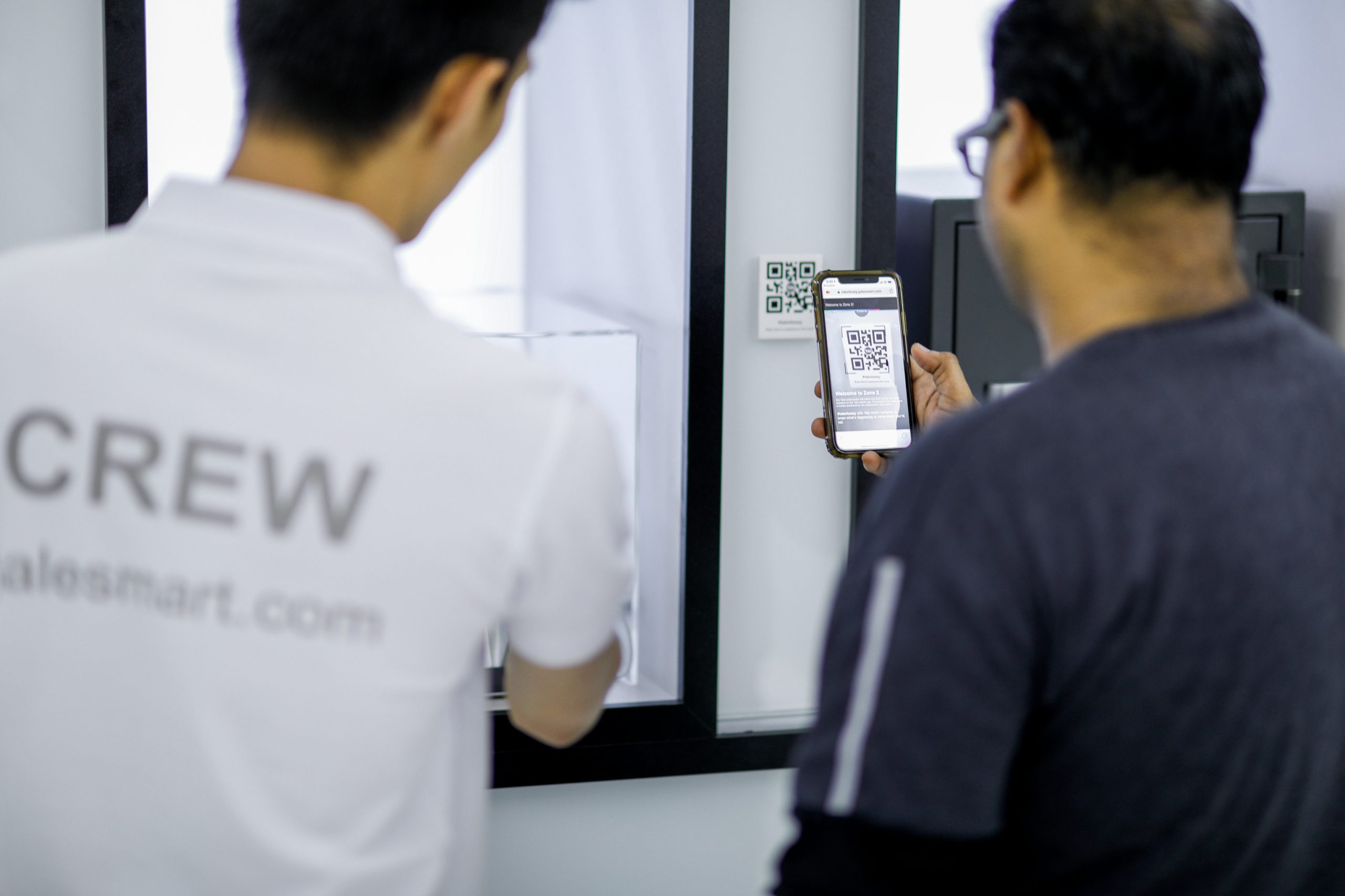 A male customer scans a QR code at the Yale Smart Shop New Retail Experience with the assistance of a brand ambassador