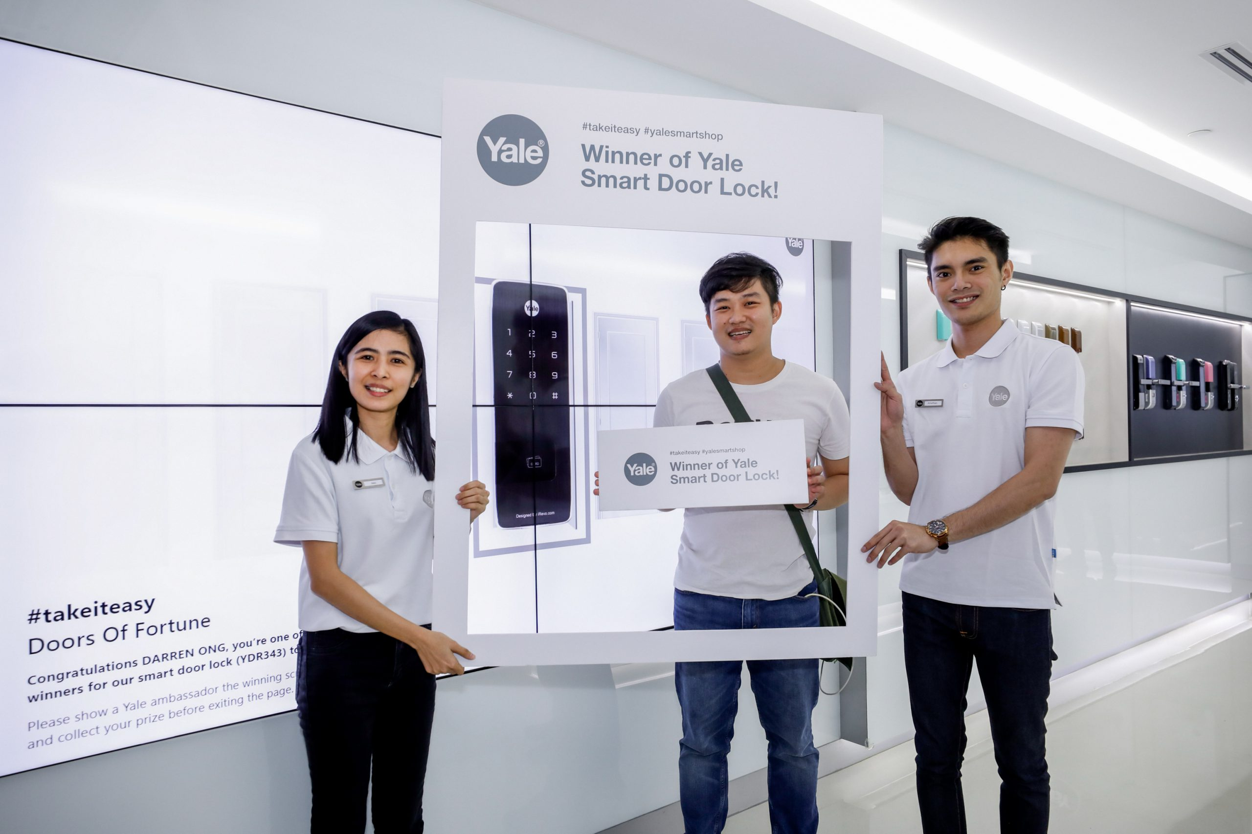 The winner of yale smart door lock posing for a picture in front of the yale interactive spin and win wall, along with two store assistants