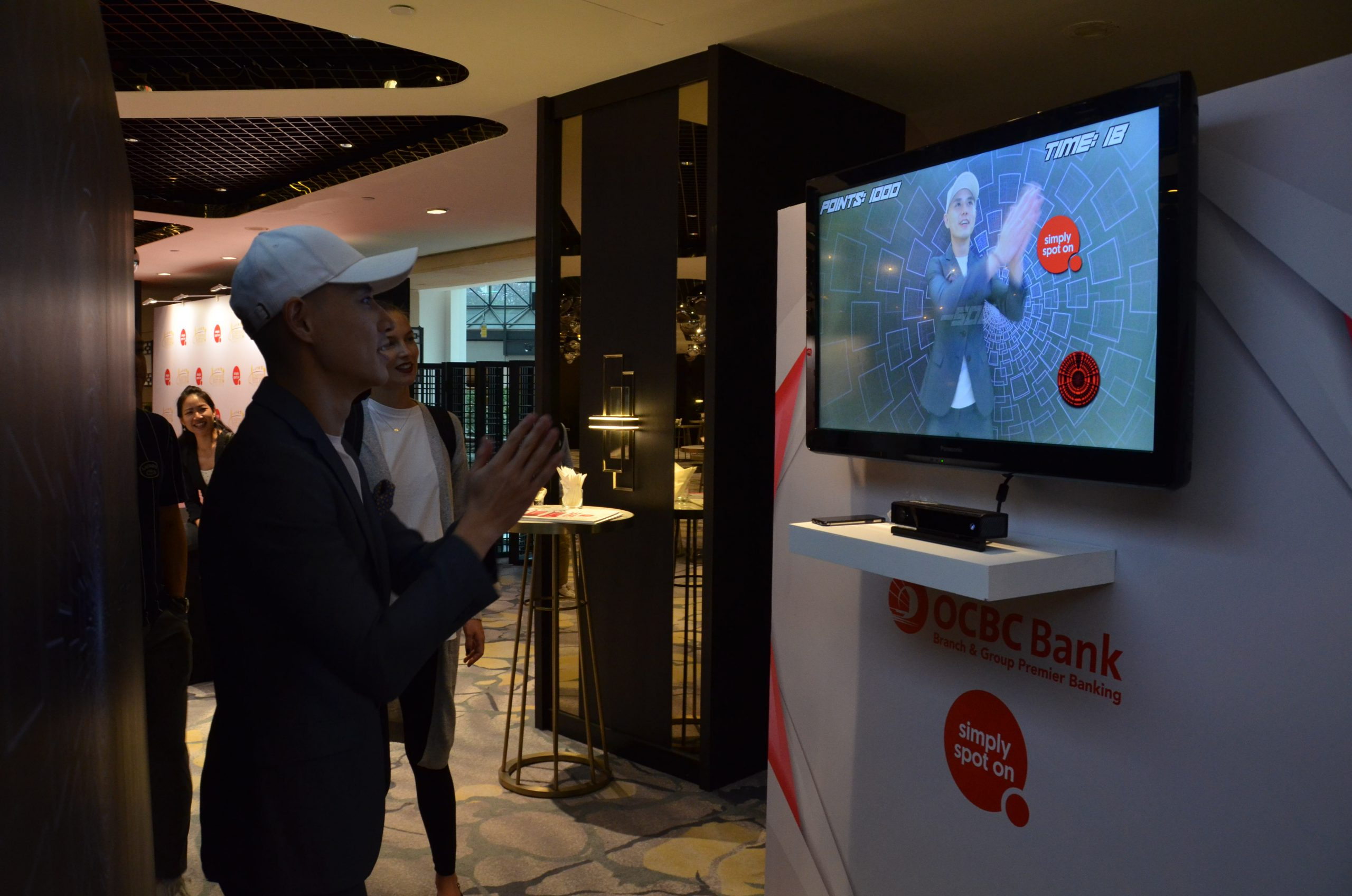 Man Interacting With OCBC Quick Reaction Game Kiosk