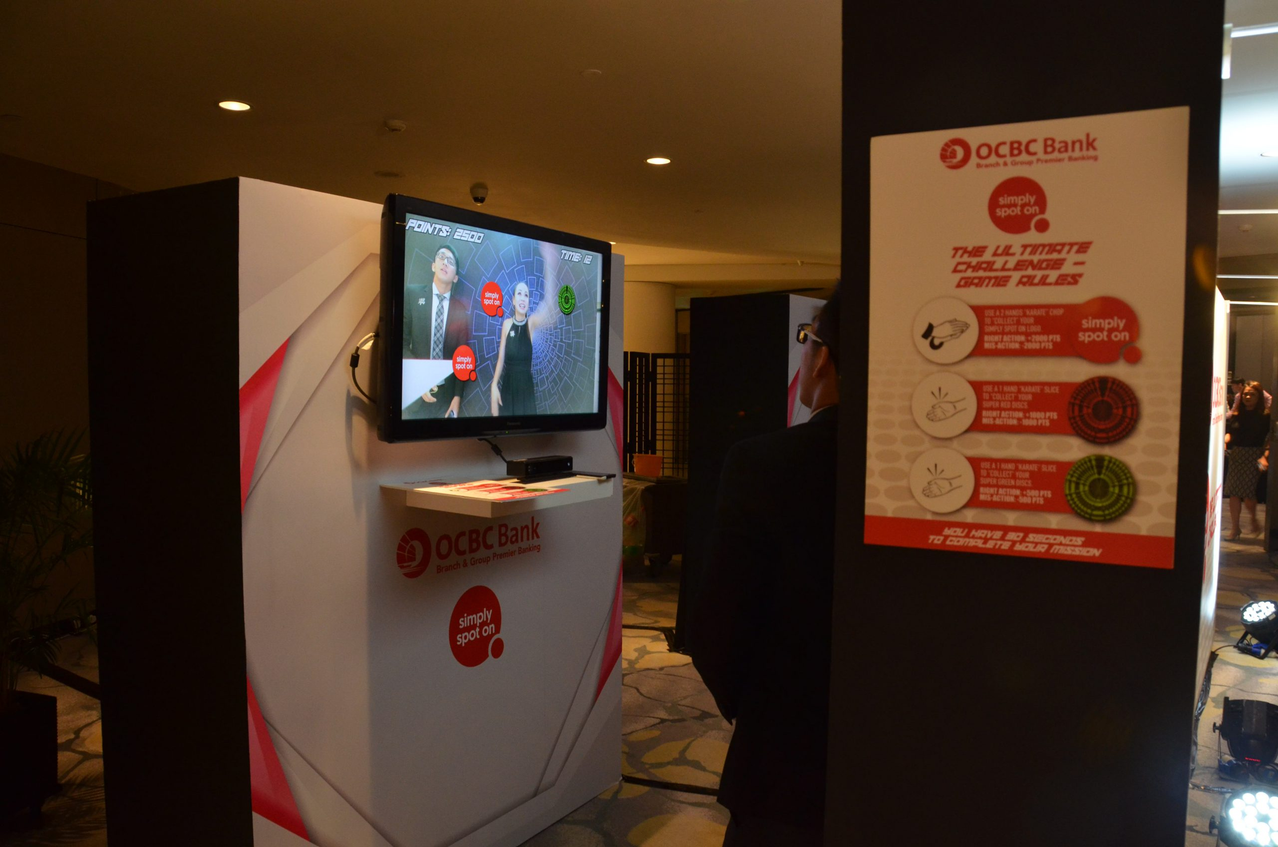 Office workers interacting with OCBC Quick Reaction Game Kiosk