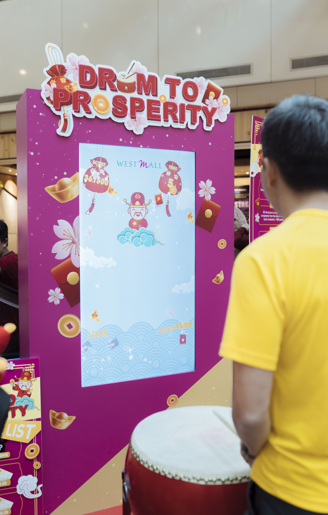 A man in yellow shirt plays the west mall drum to prosperity kiosk game