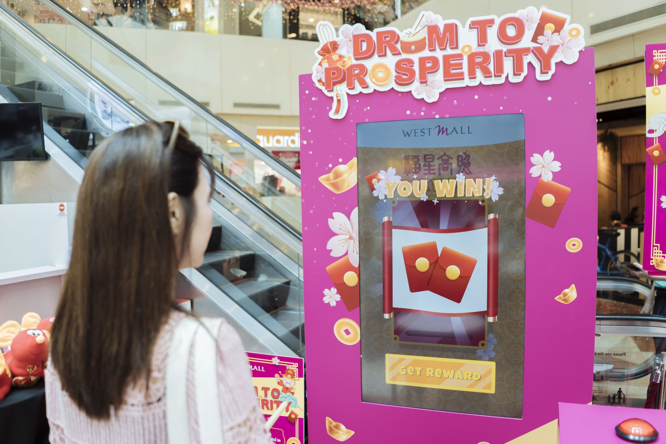 A girl won a prize after playing the west mall drum to prosperity kiosk game