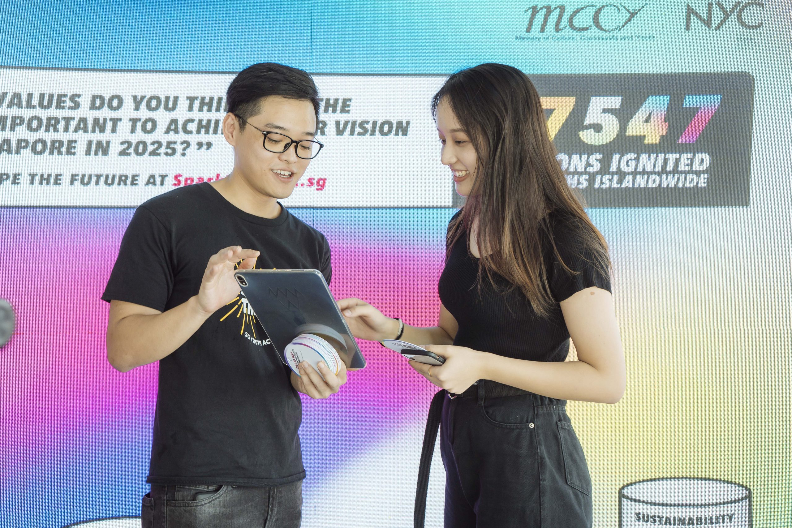 A MCCY ambassador explains to a girl how the MCCY Network Voting System works