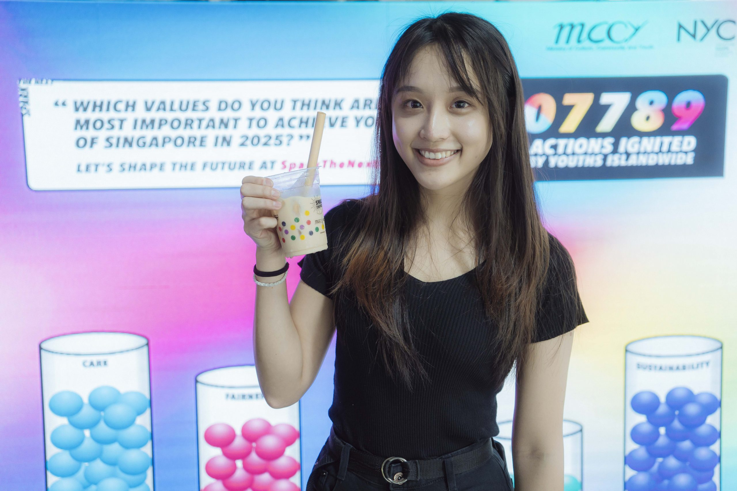 A girl poses with her free cup of bubble tea in front of the MCCY Network Voting System