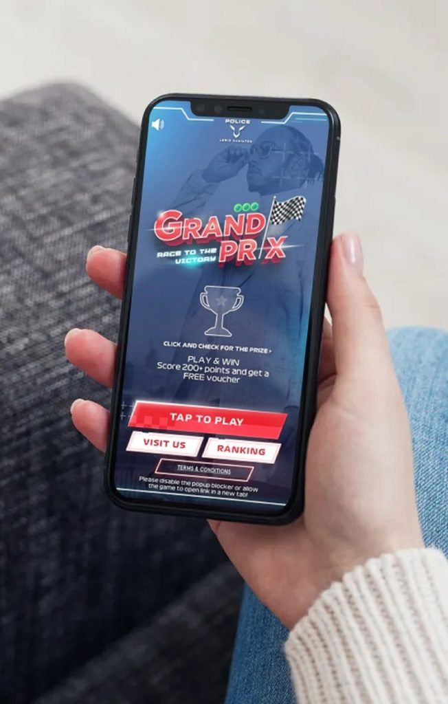 Woman in beige sweater playing the Police Lewis Hamilton Grand Prix microsite game on her smartphone